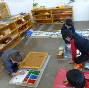 Un niño trabaja los múltiplos, mientras otros calculan volúmenes y otro ha preparado el material para investigar la evolución del ser humano