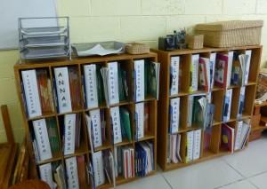 Casilleros donde cada niño tiene su archivador, cuadernos y carpeta. En la parte superior están hojas, lápices, etc.