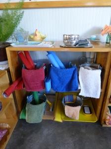 Bandejas de vida práctica de casa de niños, con todo lo necesario para la limpieza; delantales, cubos,  trapos, etc